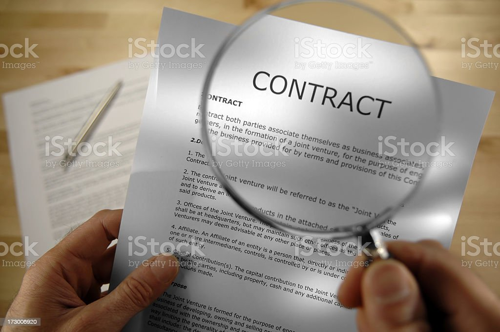 Hands holding magnifier and contract select focus stock photo