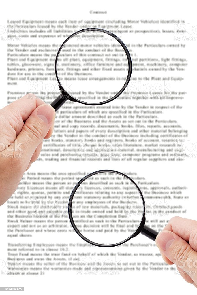 Hands holding magnifying glass reading document stock photo