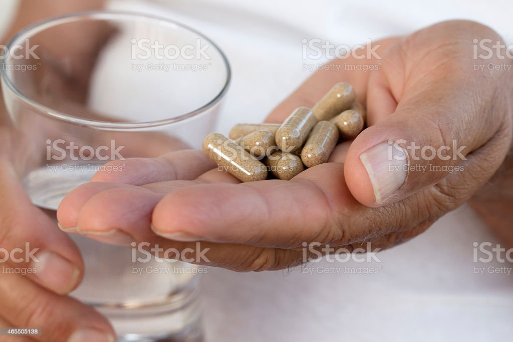 Hands holding medication in palm and glass of water in other stock photo
