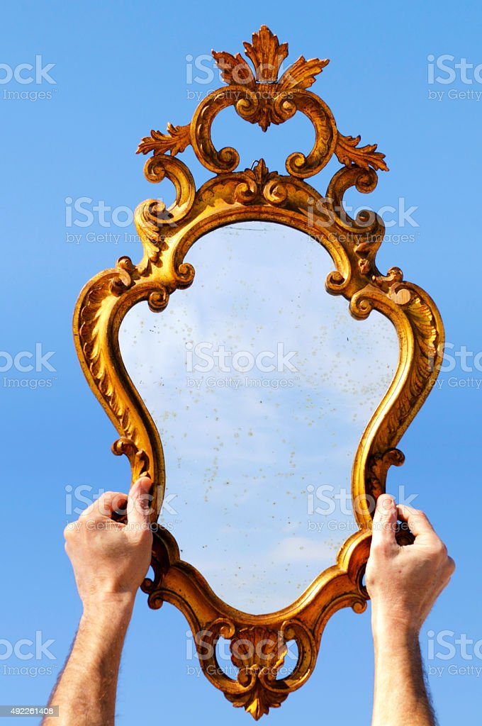 Hands holding Mirror reflecting blue sky stock photo