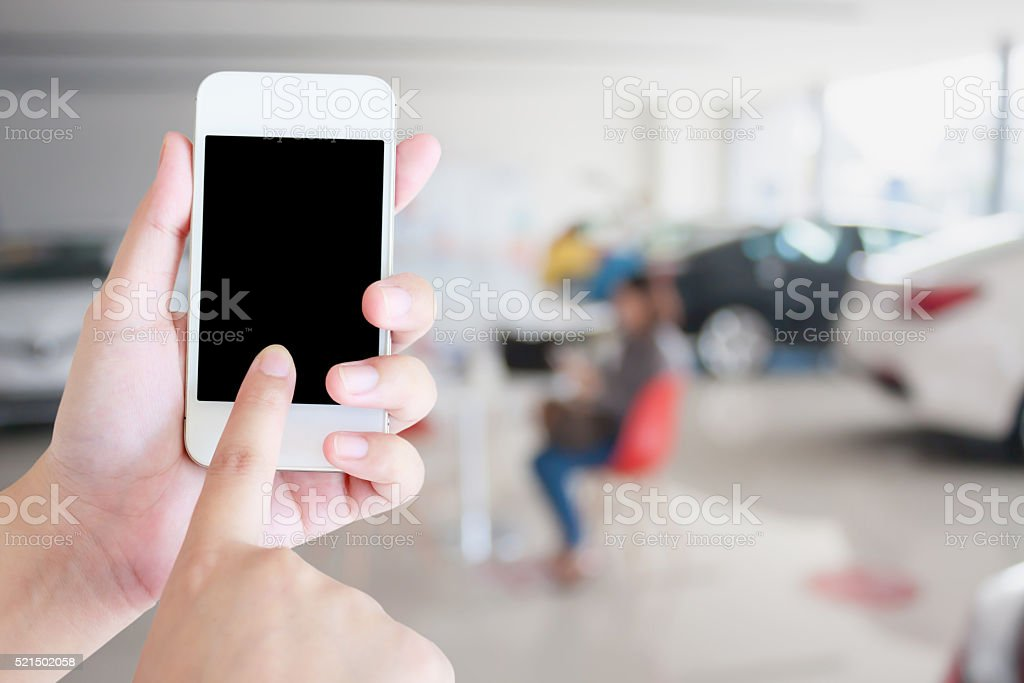 hands holding mobile phone with new cars in showroom stock photo