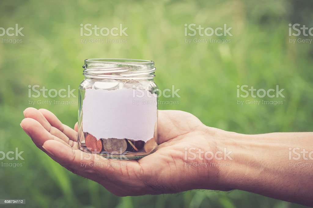 Hands holding money in the jar stock photo