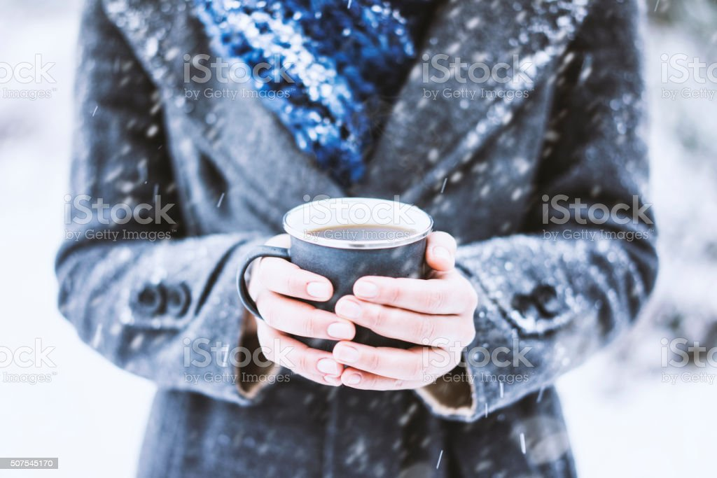 Hands holding mug in a snowy day stock photo