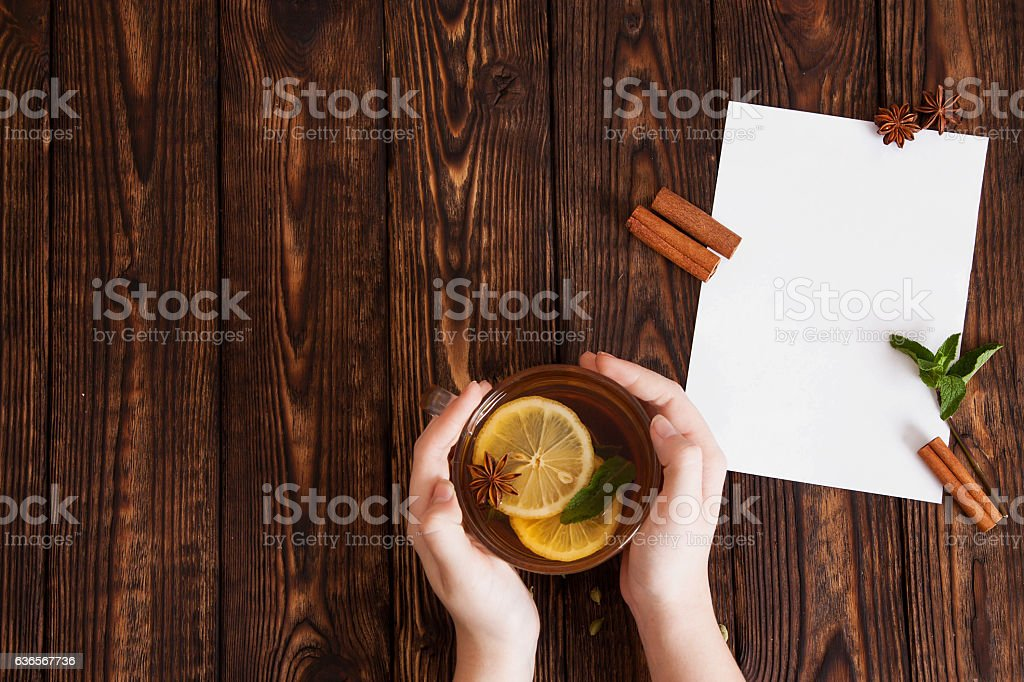 hands holding mug of tea over the table royalty-free stock photo