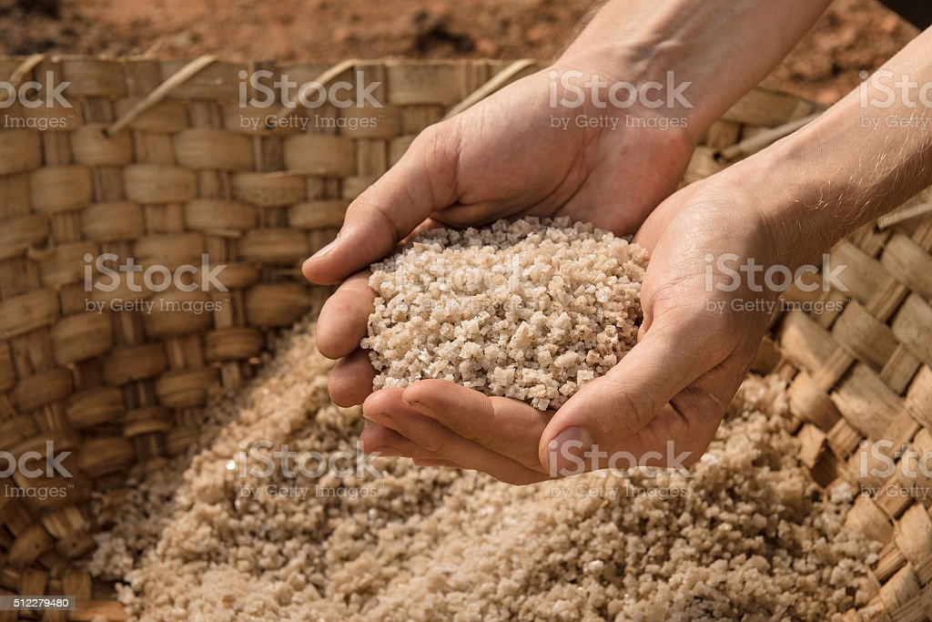 Hands holding natural salt outdoors. stock photo
