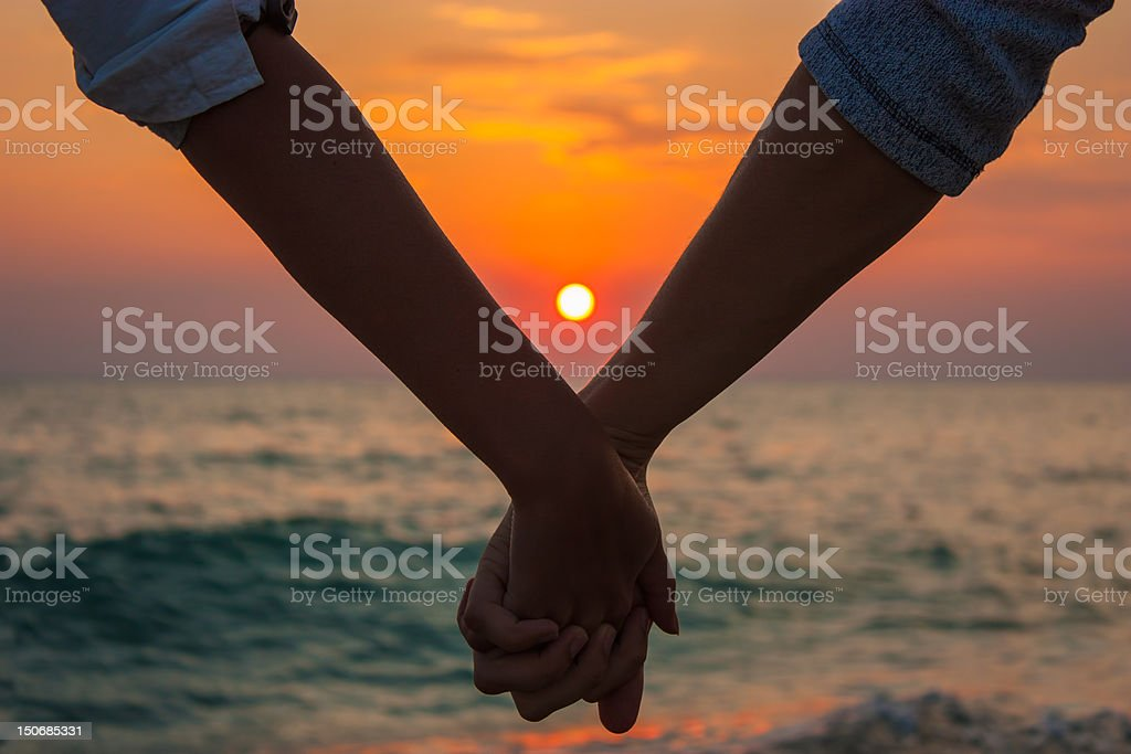 Hands holding on sunset at the sea stock photo