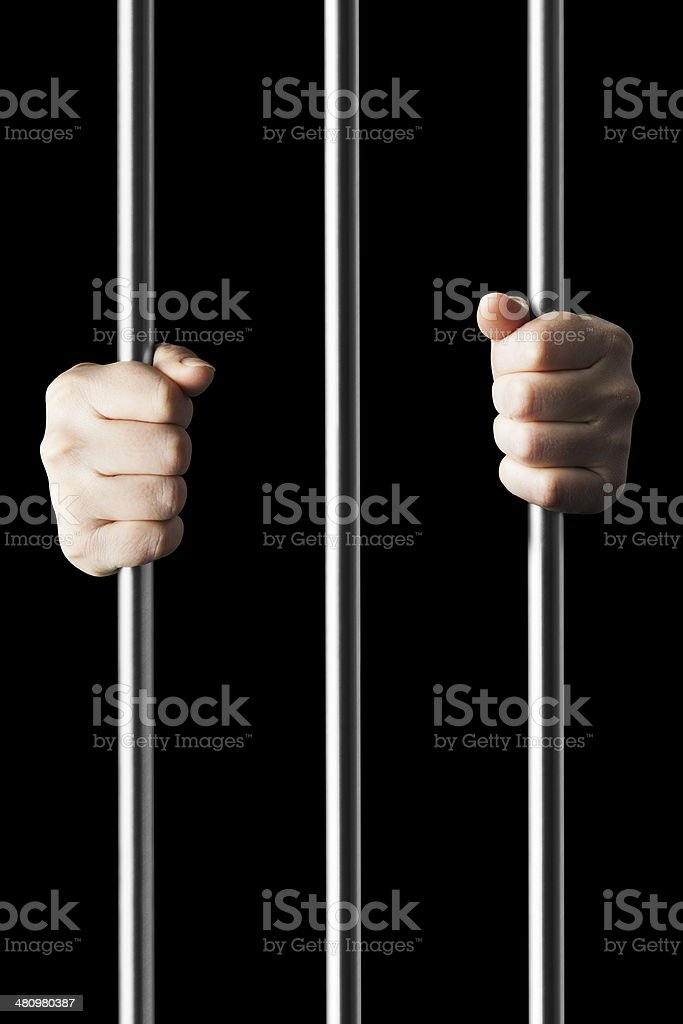 Hands holding onto prison bars from within cell stock photo