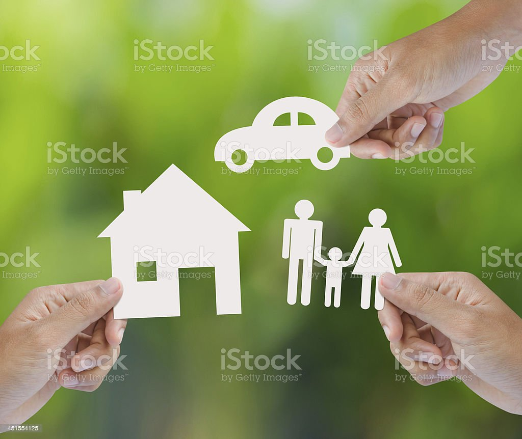 Hand holding a paper home, car, family on green background stock photo
