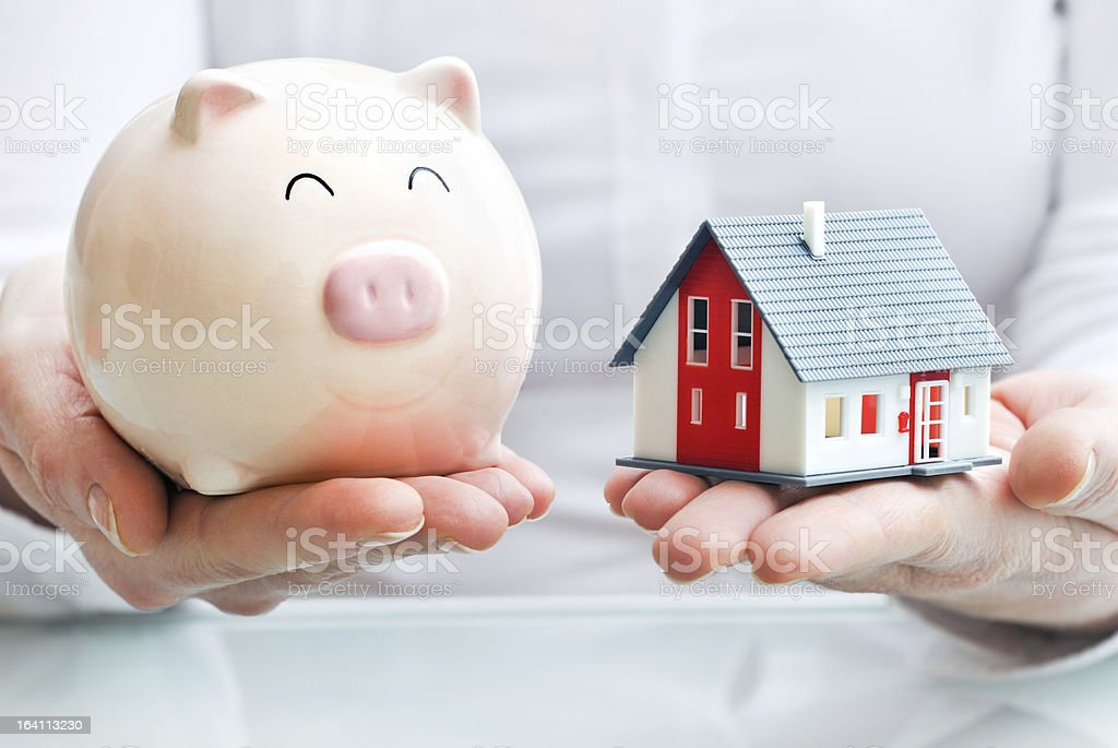 Hands holding piggy bank and  house model stock photo