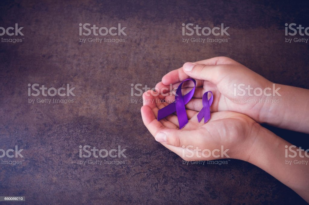 hands holding Purple ribbons,toning copy space background, Alzheimer's disease, Pancreatic cancer, Epilepsy awareness, Hodgkin's Lymphoma awareness stock photo