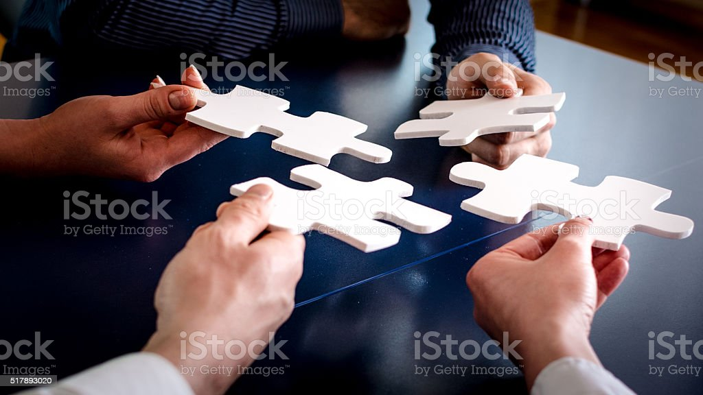 Hands holding puzzle pieces stock photo