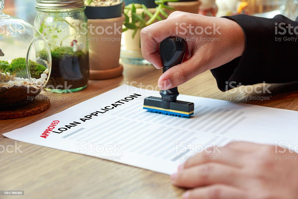 Hands holding rubber stamp with approved loan application on desk stock photo