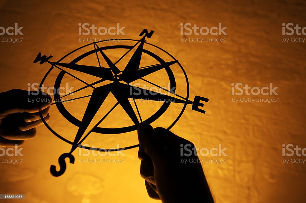 Hands Holding Silhouette of Compass by Glowing Stone Wall stock photo