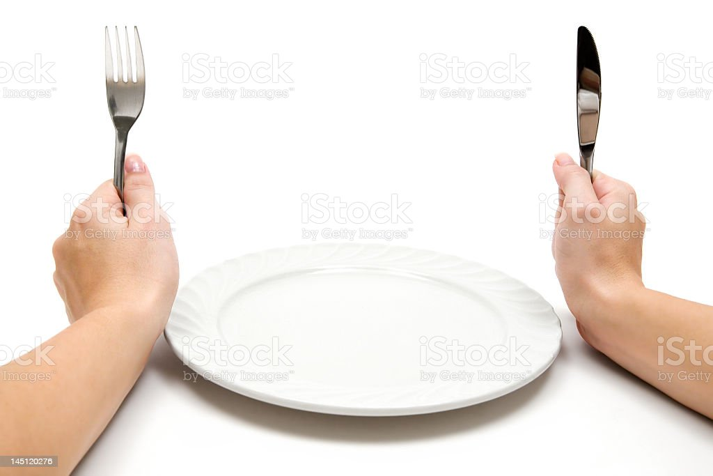 Hands holding silverware in front of an empty plate stock photo