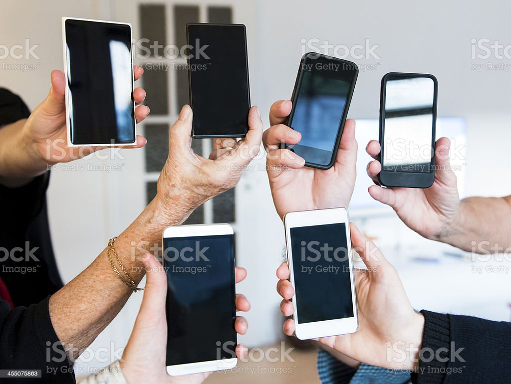 Hands holding six different mobile phones stock photo