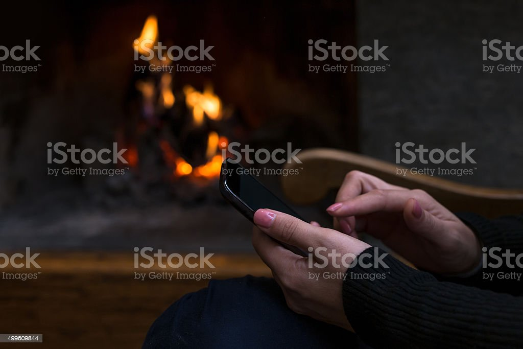 Fireplace Design fireplace background : Hands Holding Smartphone Against Fireplace Background stock photo ...
