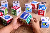 Hands holding social media cubes