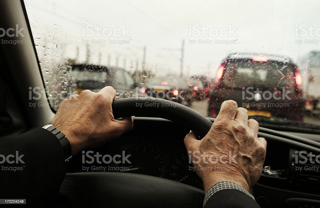 Hands holding steering wheel on traffic jam on a rainy day stock photo