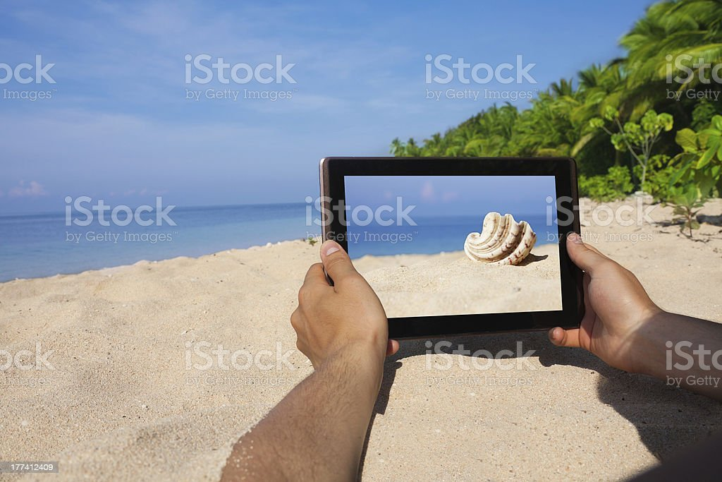 hands holding tablet pc on beach royalty-free stock photo