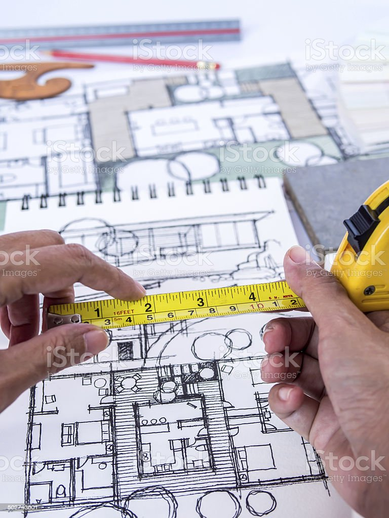 Hands holding tape measure, home renovation with architecture drawing concept stock photo
