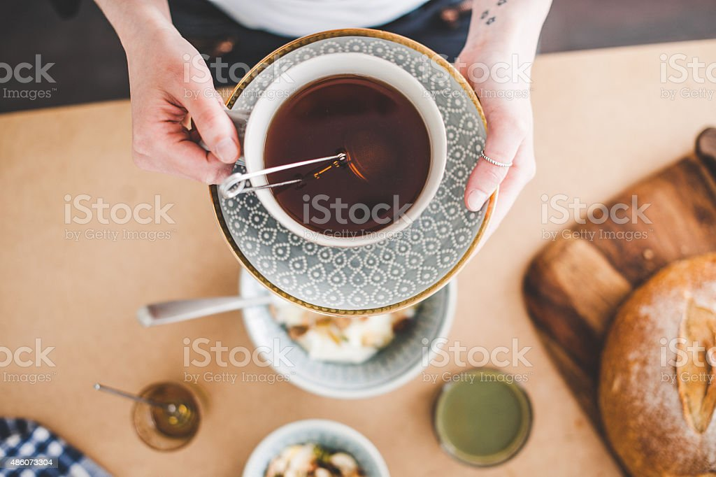 Hands holding tea cup over the breakfast table. stock photo