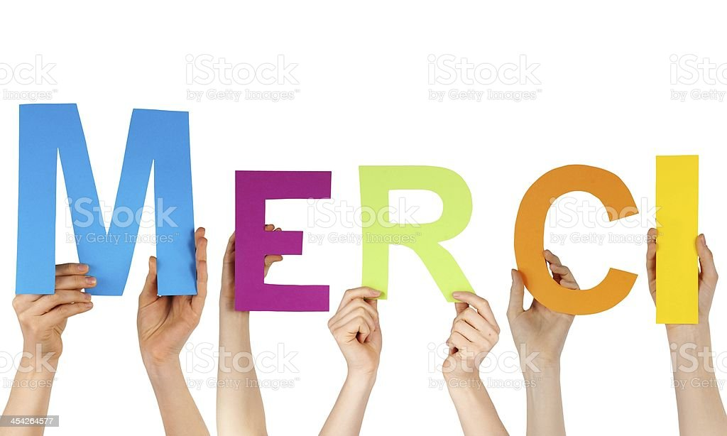 hands holding the letters MERCI stock photo