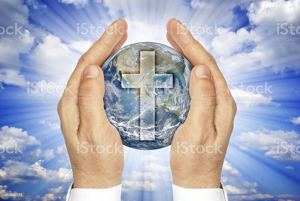 Hands holding the planet Earth with Christian cross. stock photo