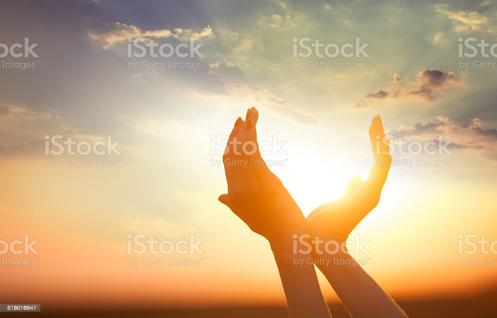 hands holding the sun at dawn stock photo