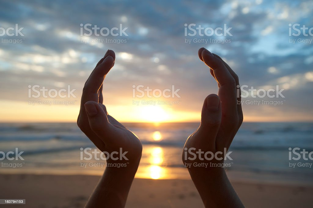 Hands holding the sunrise stock photo