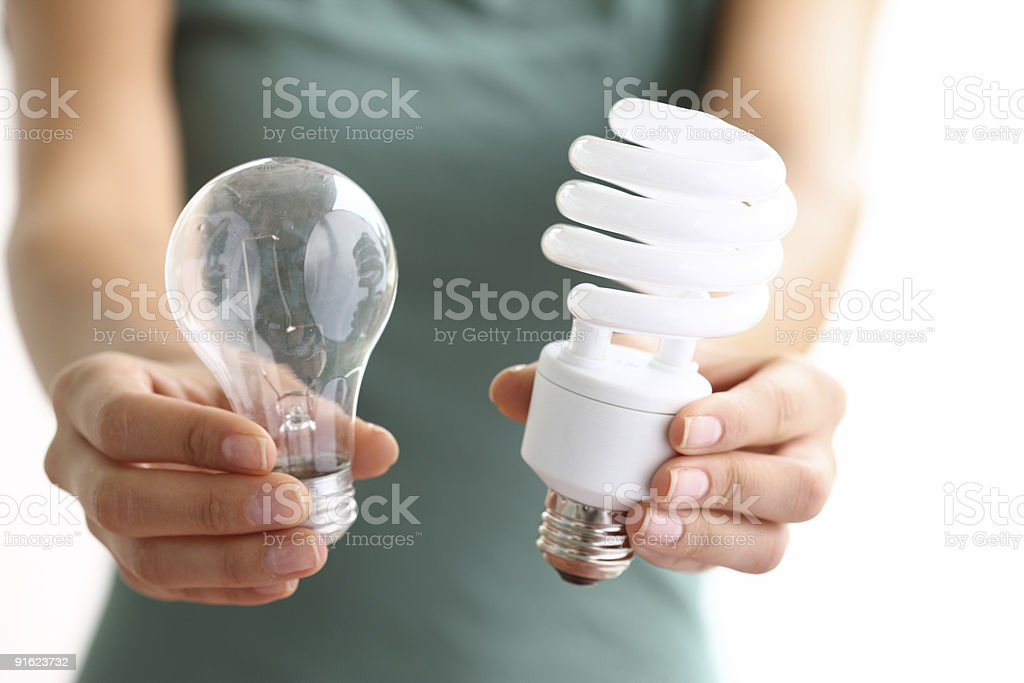 Hands holding traditional and energy efficent lightbulbs stock photo