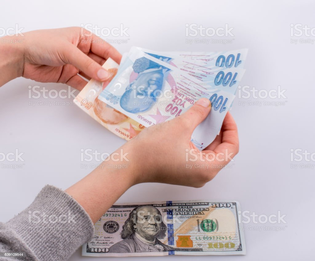 Hands holding Turksh Lira banknotes by Dollar stock photo