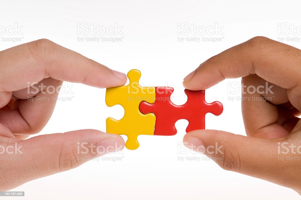 Hands holding two different colored puzzle pieces together royalty-free stock photo