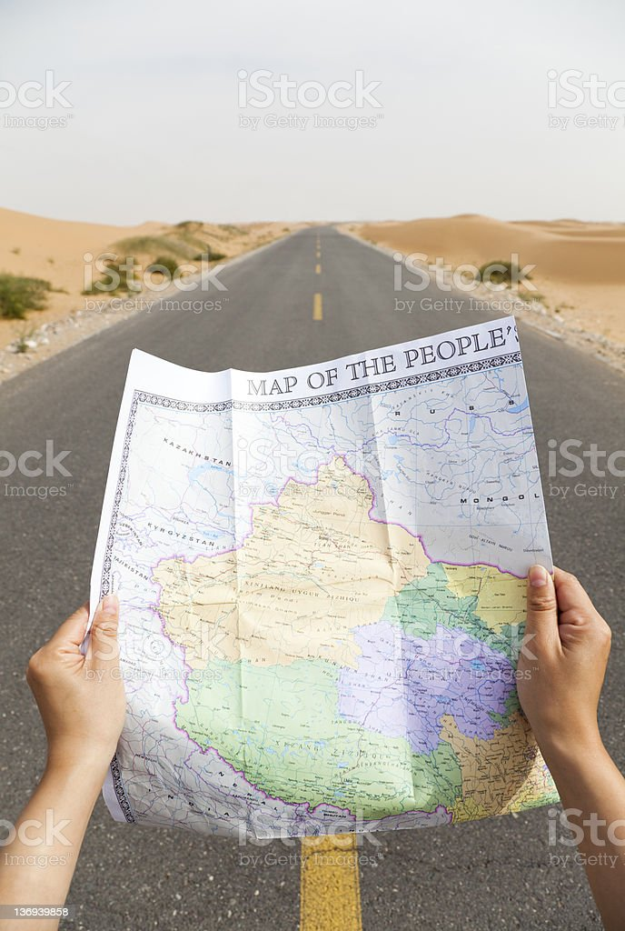 Hands holding up a map, looking down the road stock photo