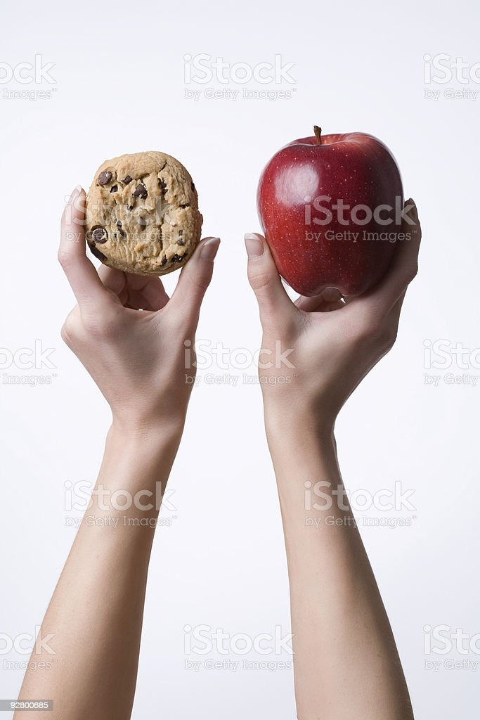 Hands holding up an apple and cookie stock photo