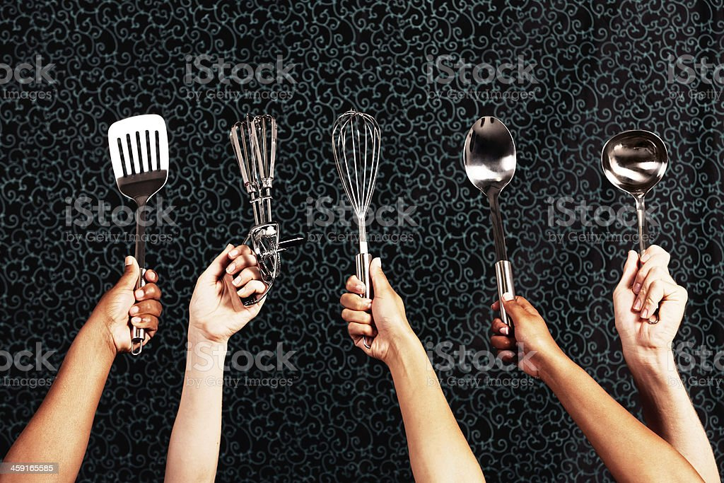 Hands holding various kitchen tools against dark background stock photo