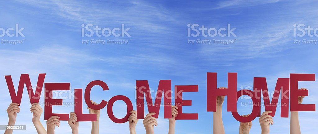 Hands Holding Welcome Home in the Sky stock photo