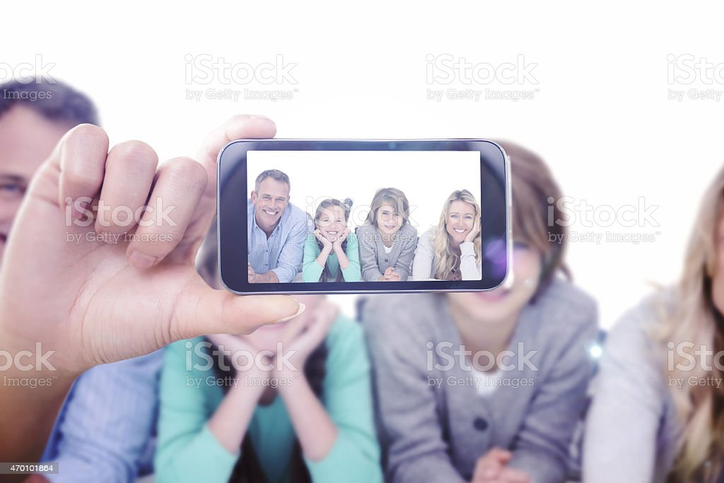 A hands holds a cellphone and takes a picture of a family stock photo