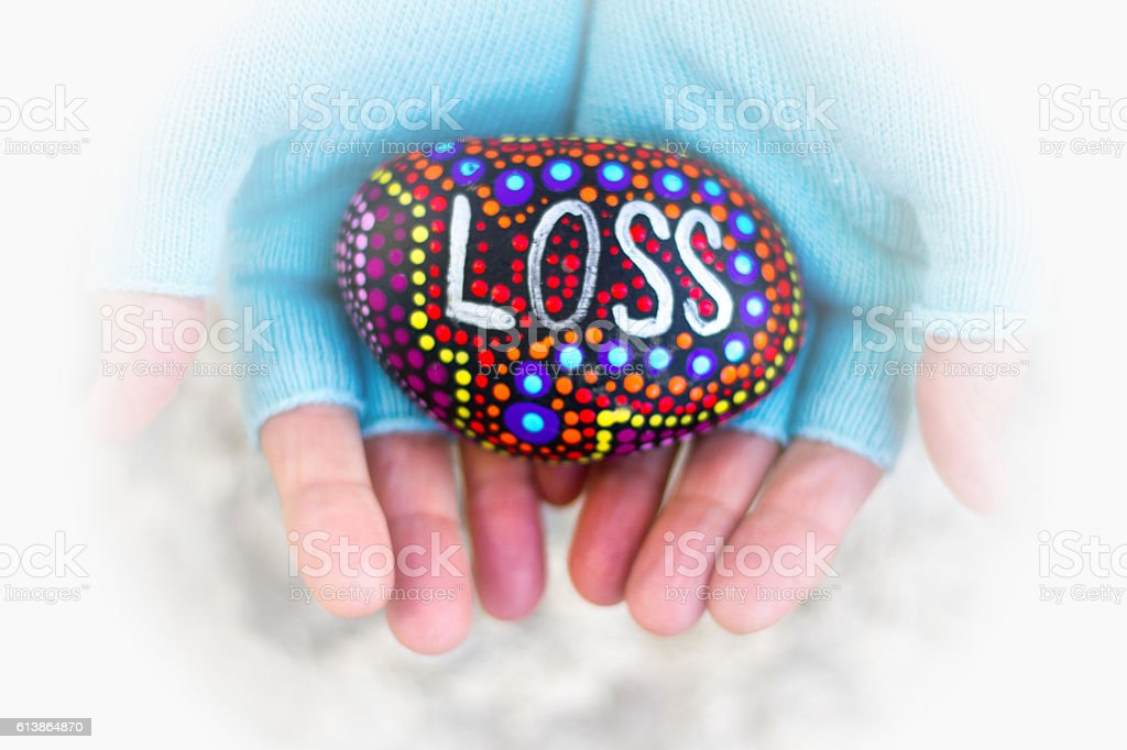 Hands Holidng Colorful Painted Rock with Word 'LOSS' stock photo