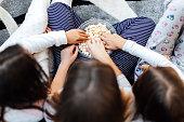 Hands In Bowl Full Of Popcorn