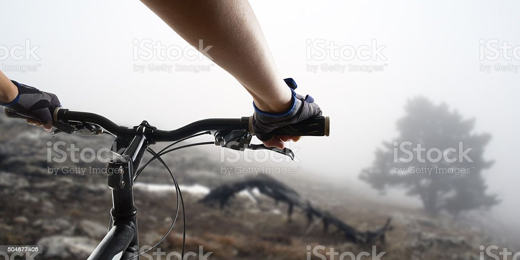 Hands in gloves holding handlebar of a bicycle. Mountain Bike stock photo