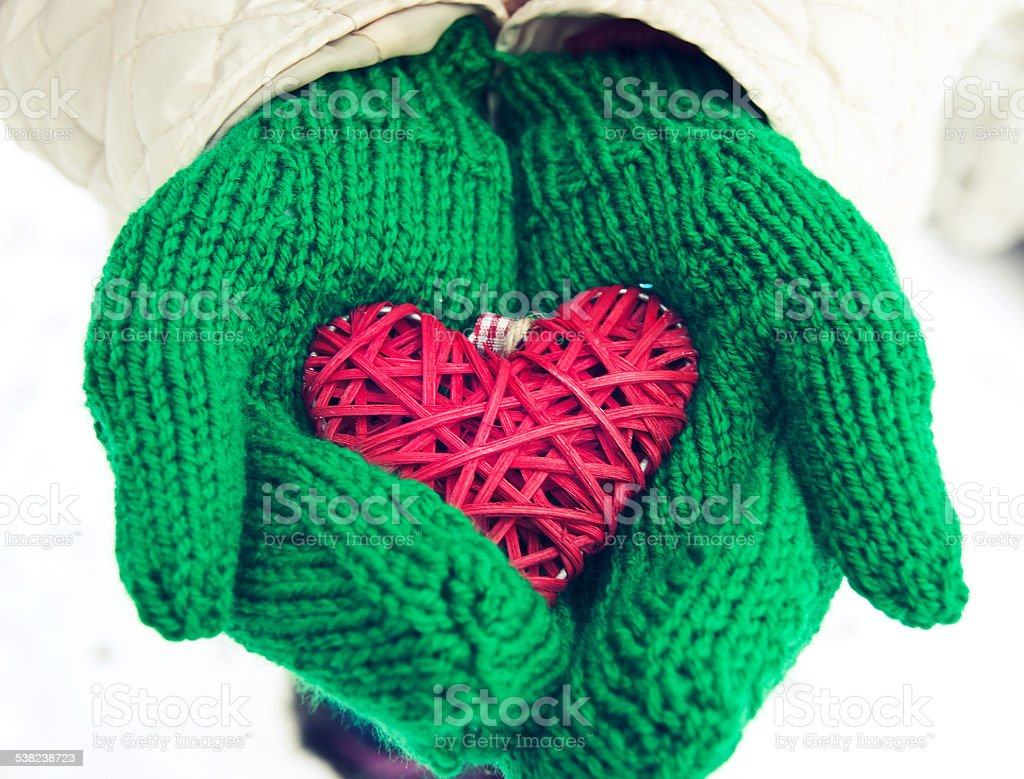 hands in green woolen mittens holding red heart stock photo