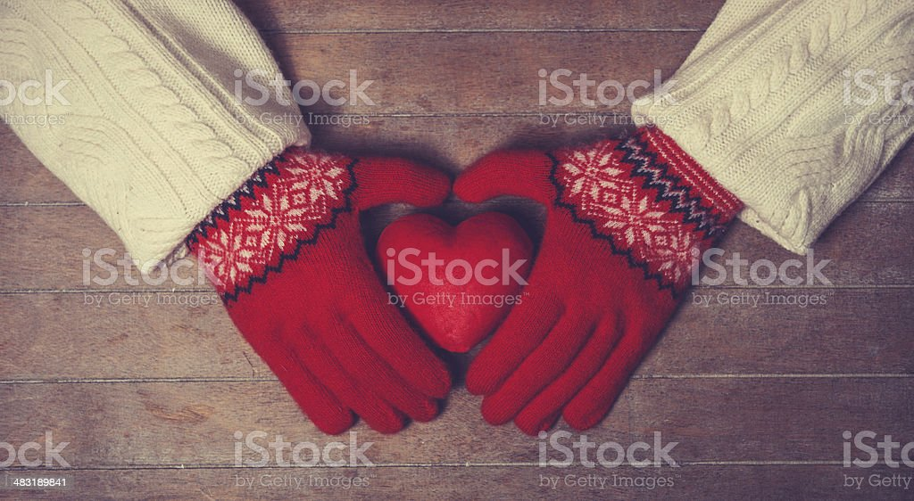 Hands in mittens holdin heart toy stock photo