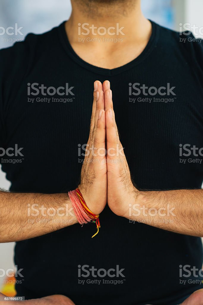 Hands in Namaste prayer mudra by Indian man practicing yoga stock photo