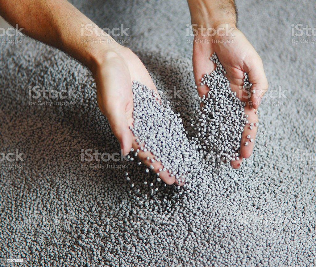 Hands in Plastic Pellets stock photo