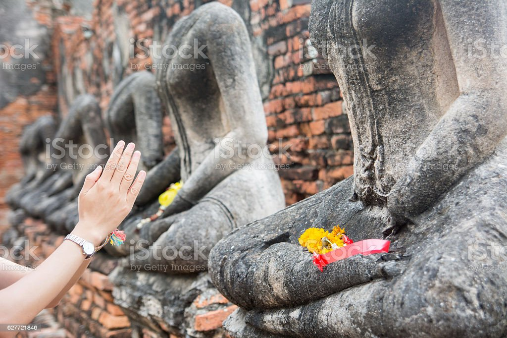 hands in pray in front of Buddha in Ayutthaya Thailand stock photo