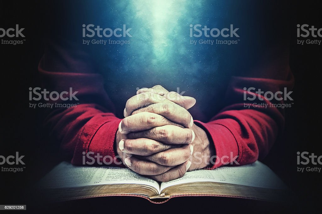 Hands in prayer over a bible stock photo