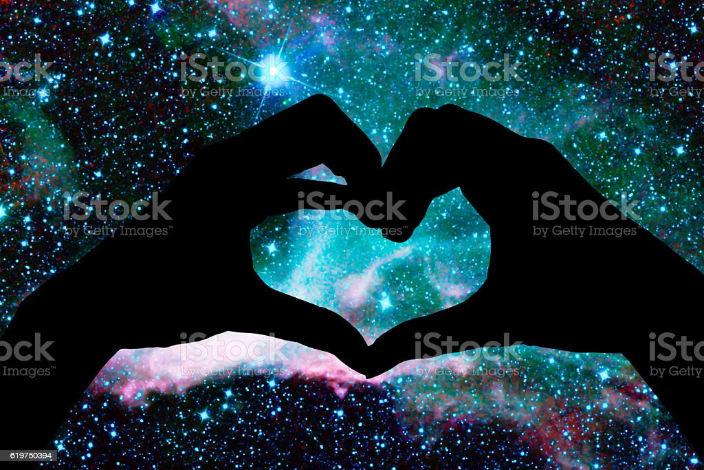 Hands in the shape of a heart, starry night background stock photo