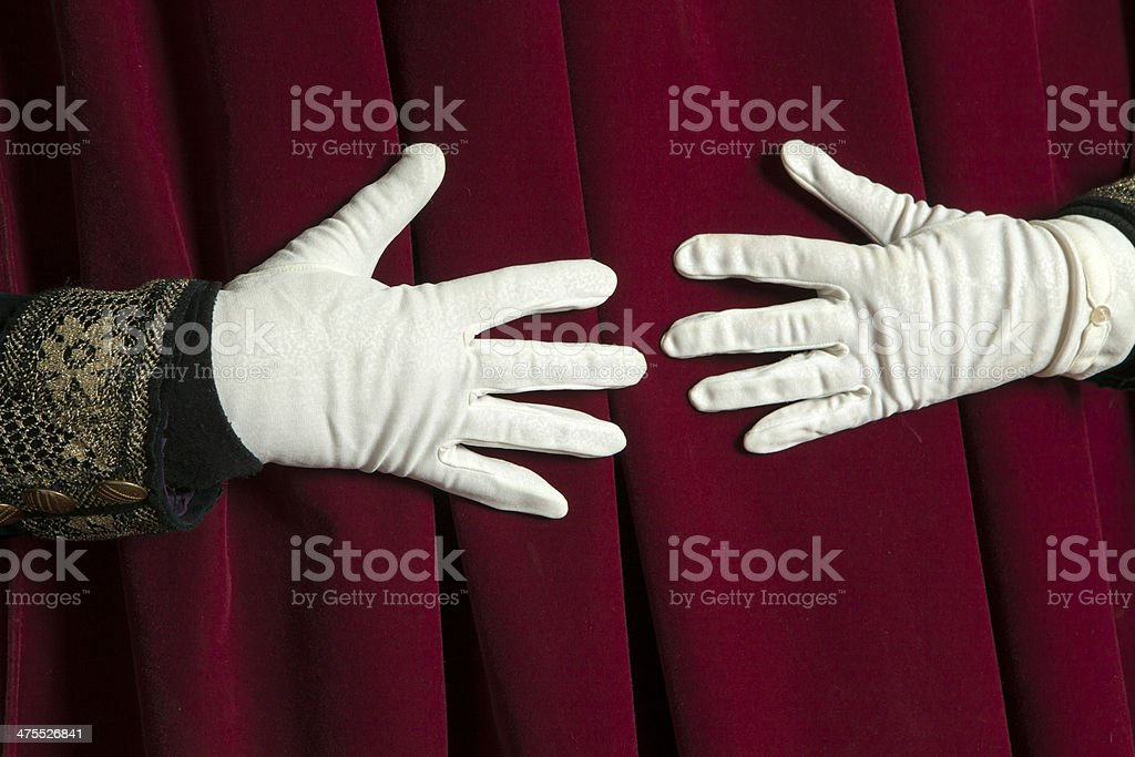 Hands in white gloves unveil the curtain. stock photo
