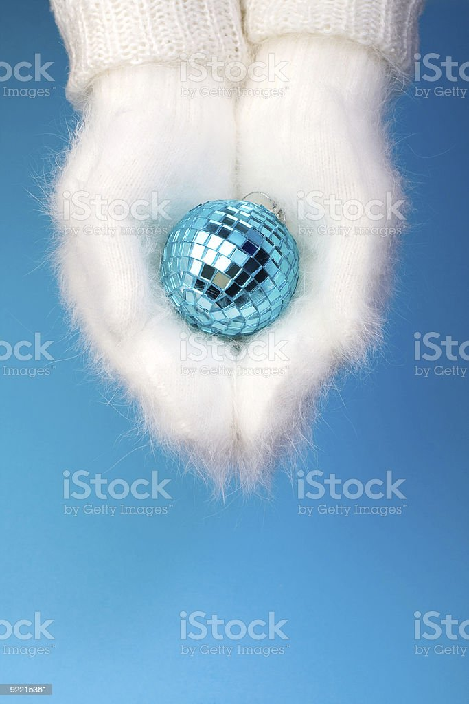 Hands in white winter mittens holding disco ball royalty-free stock photo