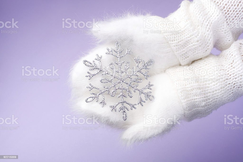 Hands in white winter mittens holding snowflake royalty-free stock photo